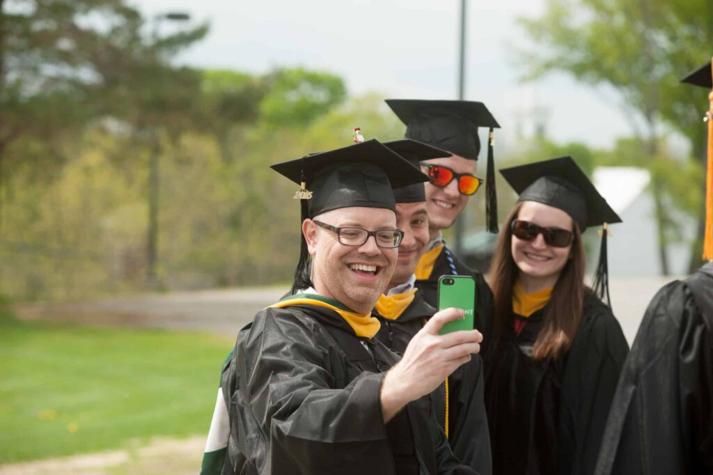 Graduate takes selfie with phone, smiling people stand behind him