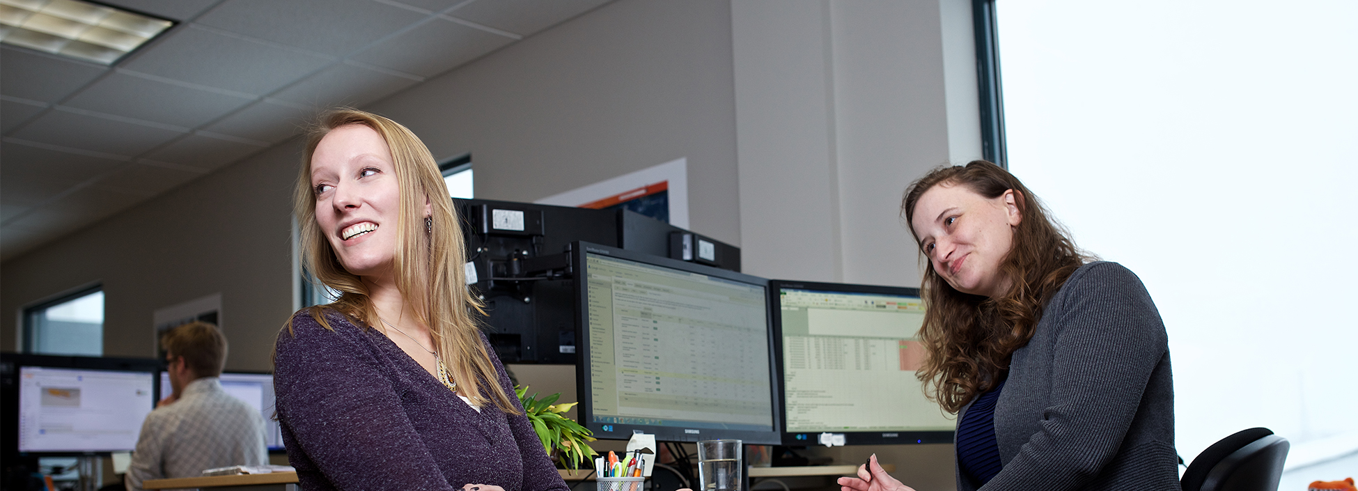 Two employees are sitting near a computer station, smiling at something off to the left not seen in the photo.