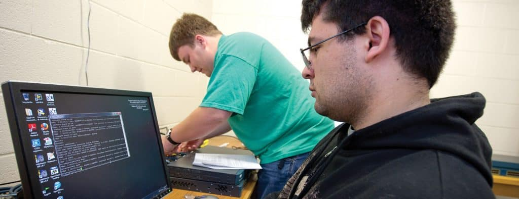 Two students work on IT equipment on the Randolph Center campus.
