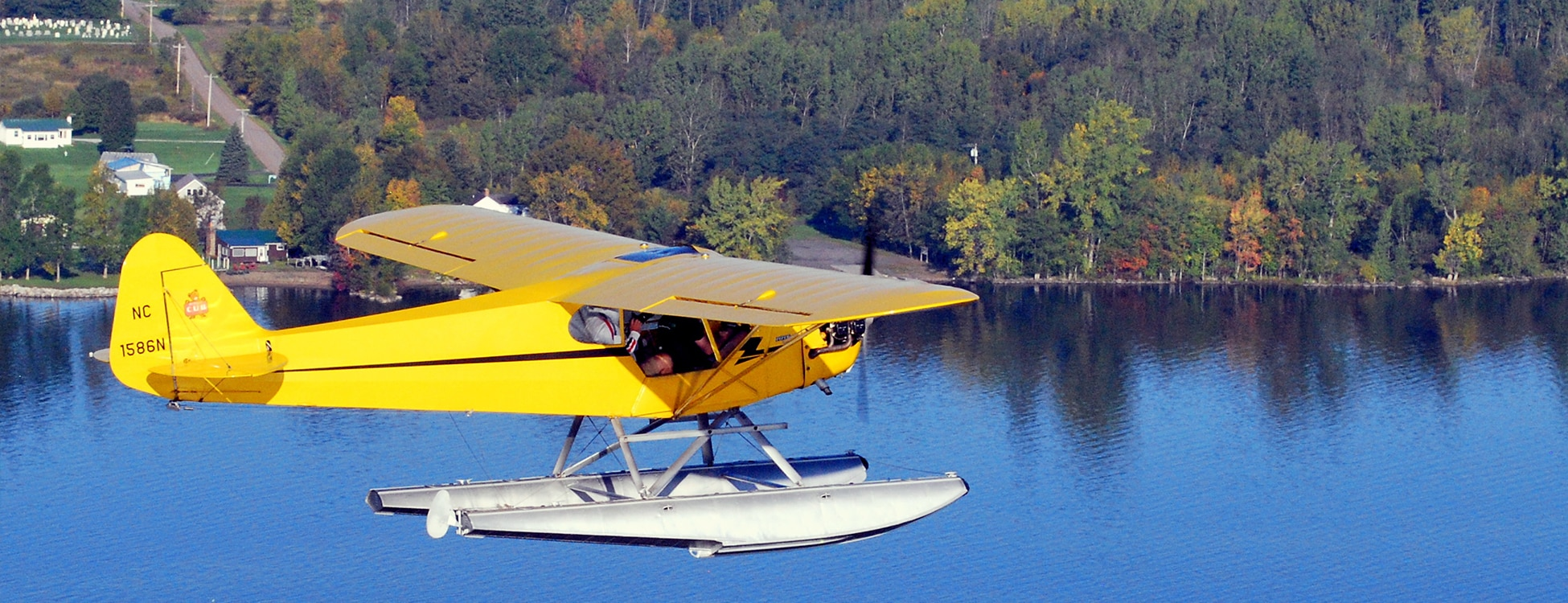Yellow plane with floats flies about the water
