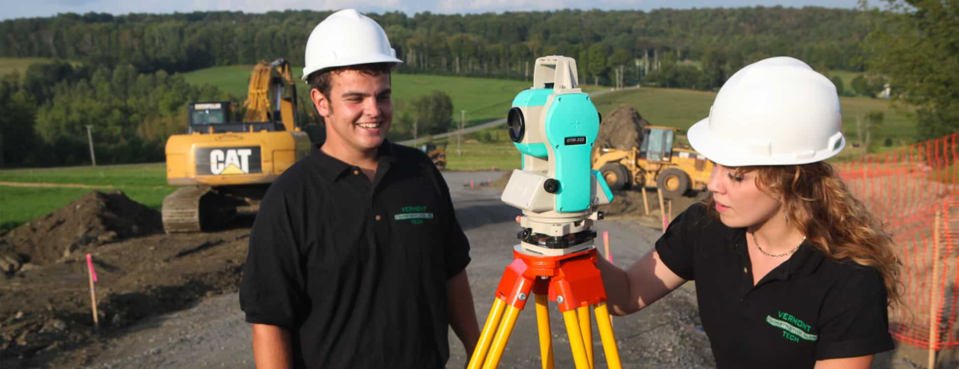 Students work with surveying equipment while on a construction management job site