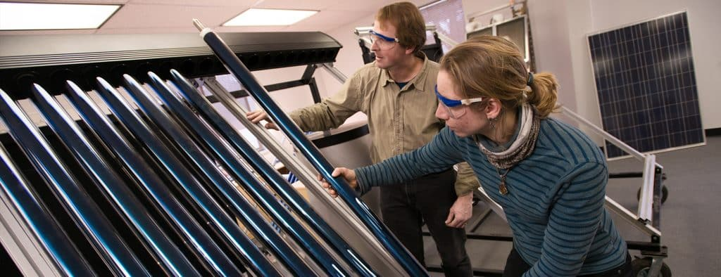 Faculty member John Kidder works with female student in the renewable energy lab, Randolph Center campus