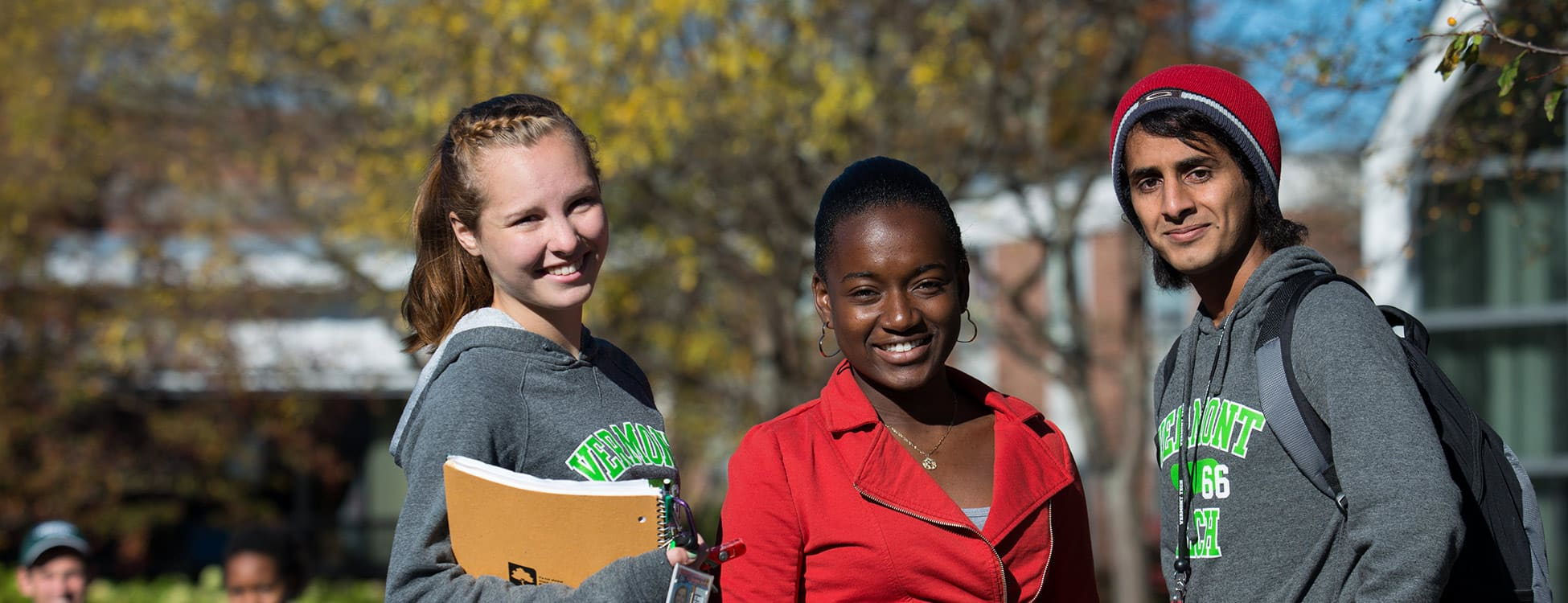 Three students posing for a picture on the plaza outside on the Randolph Center campus, diversity