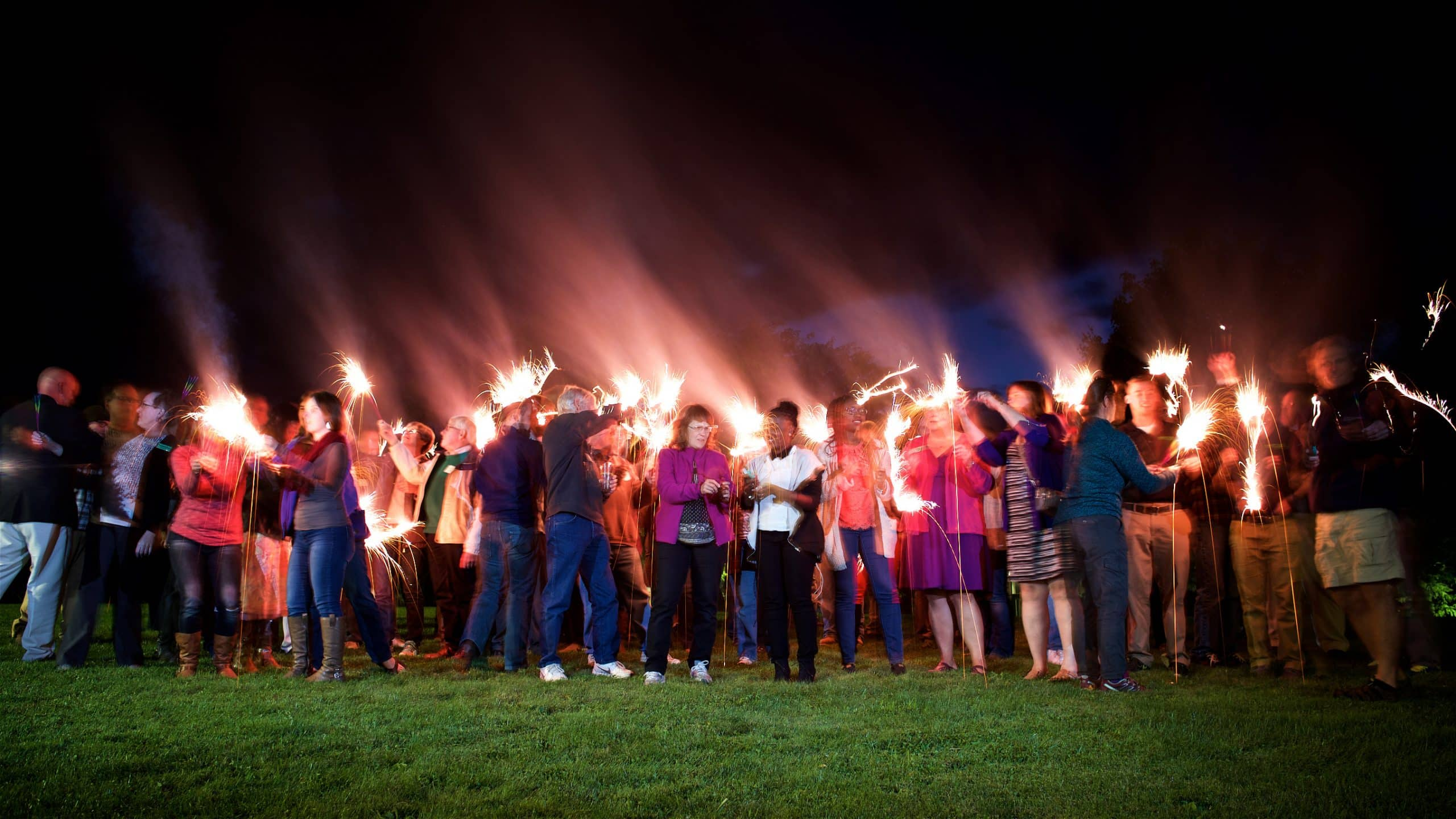 Group photo of everyone with their sparklers during the evening portion of the event.