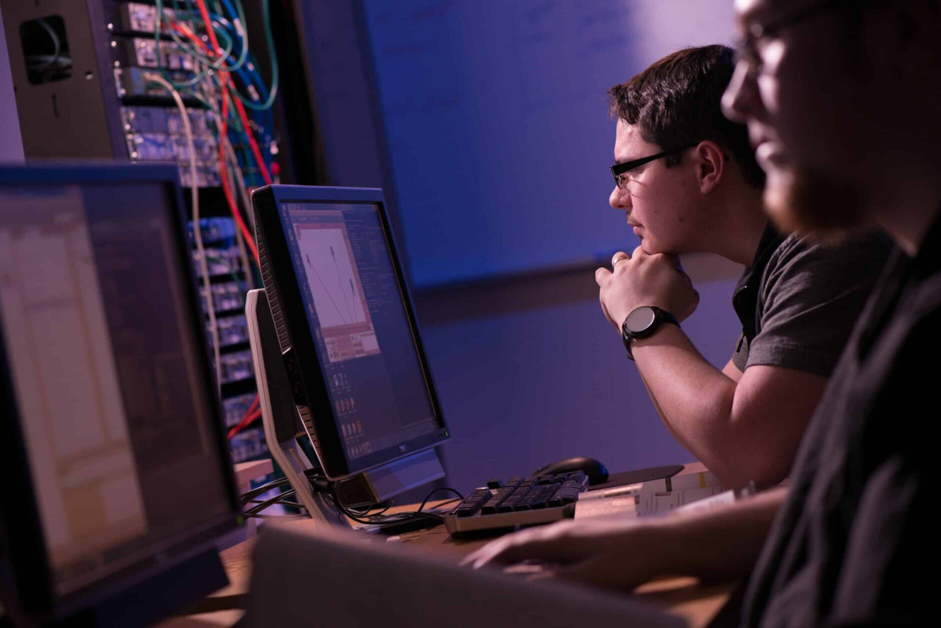 Two male students work on computer screen coding in a dimly sit room with computer wires and books.