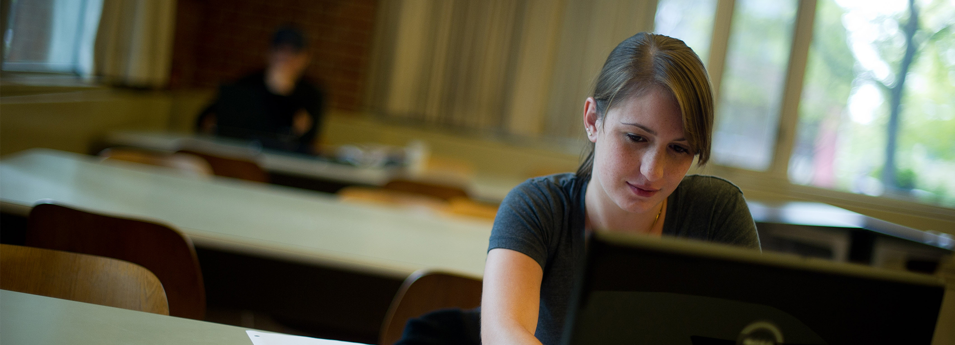 An applied business students works on an online class on her laptop