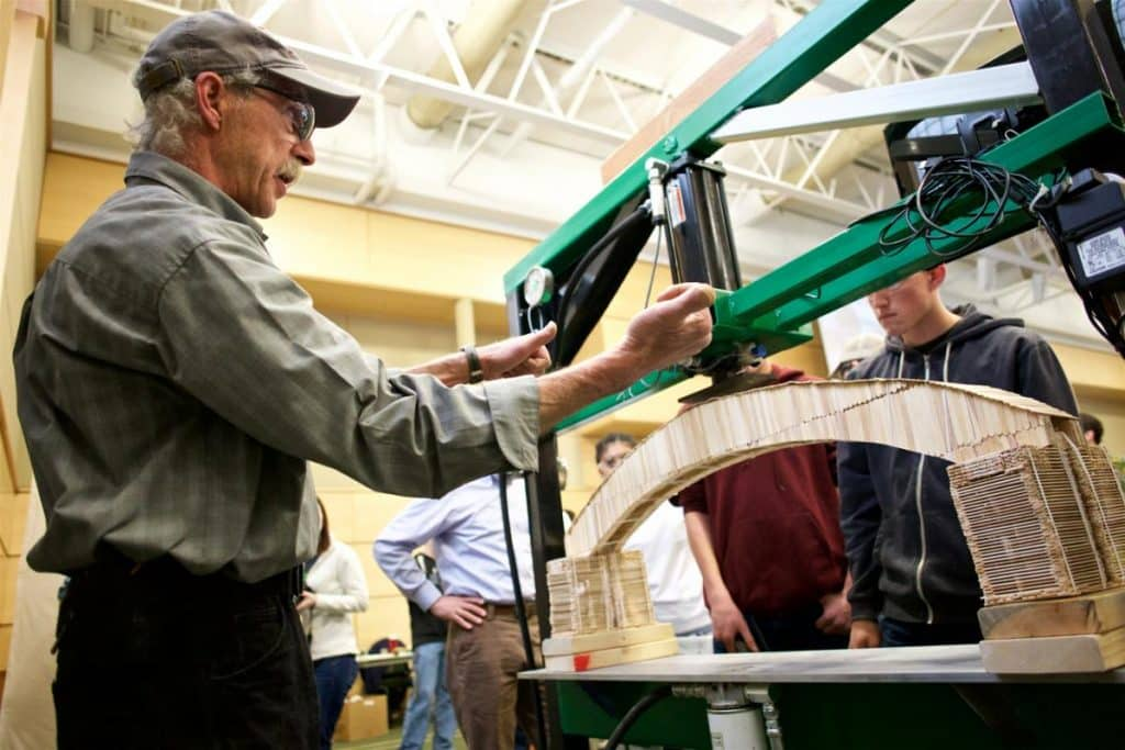 Geoff Finkles readies the machine to break the Popsicle stick bridges at the Bridge Building competition on the Randolph Center campus