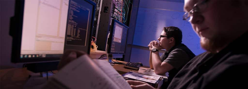 Two computer students work at computer screens with code in a dimly lit room