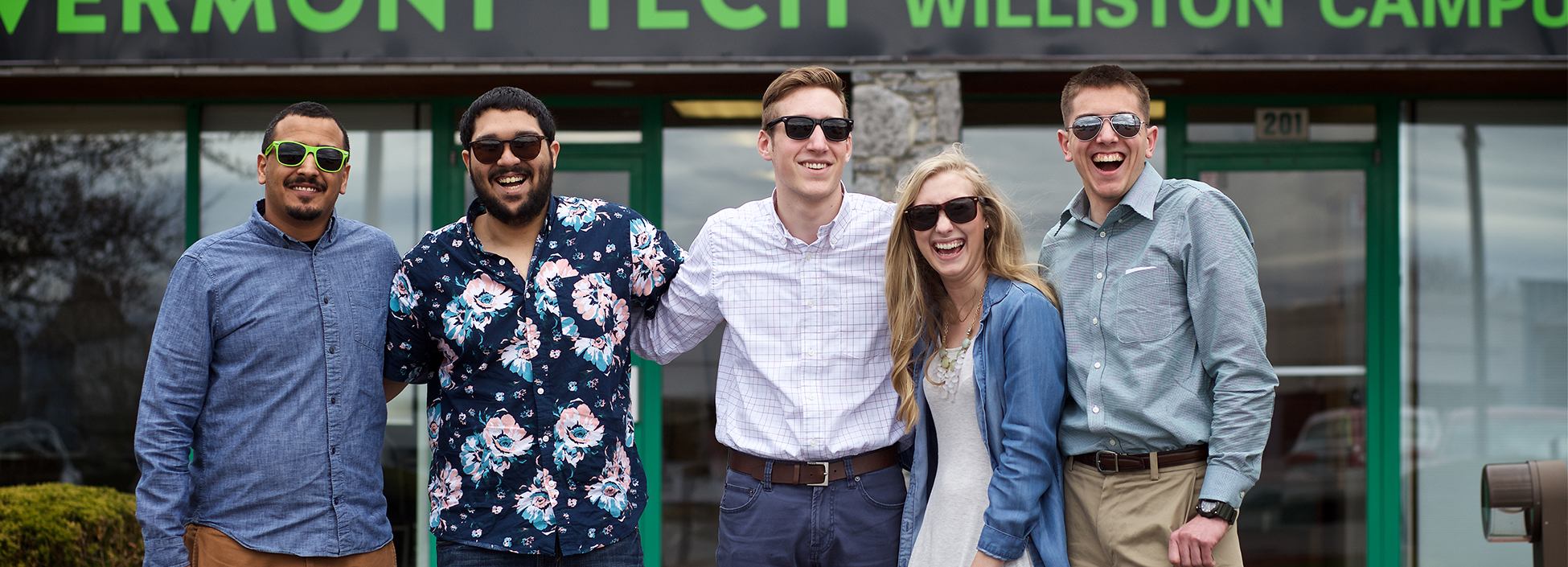 Five Vermont Tech students wearing sunglasses stand outside the Williston Campus Administration building