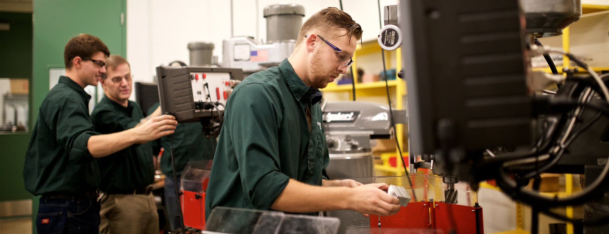 Male student works with a metal lathe machine in the manufacturing lab on the Randolph Center campus.