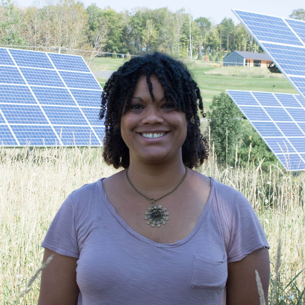 Female student stands in front of solar panels on the Randolph Center campus where she is a student in the renewable energy program.
