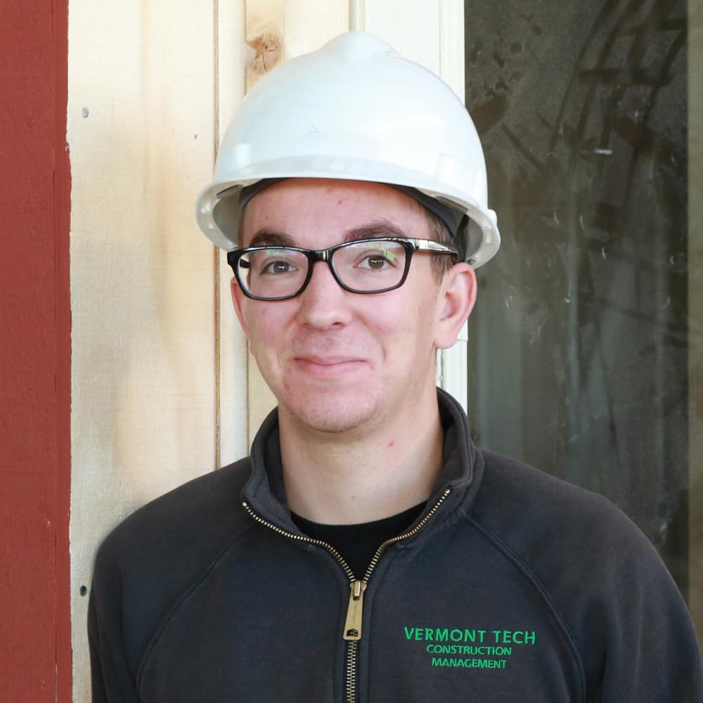 A male construction student wearing a hard hat smiles at the camera