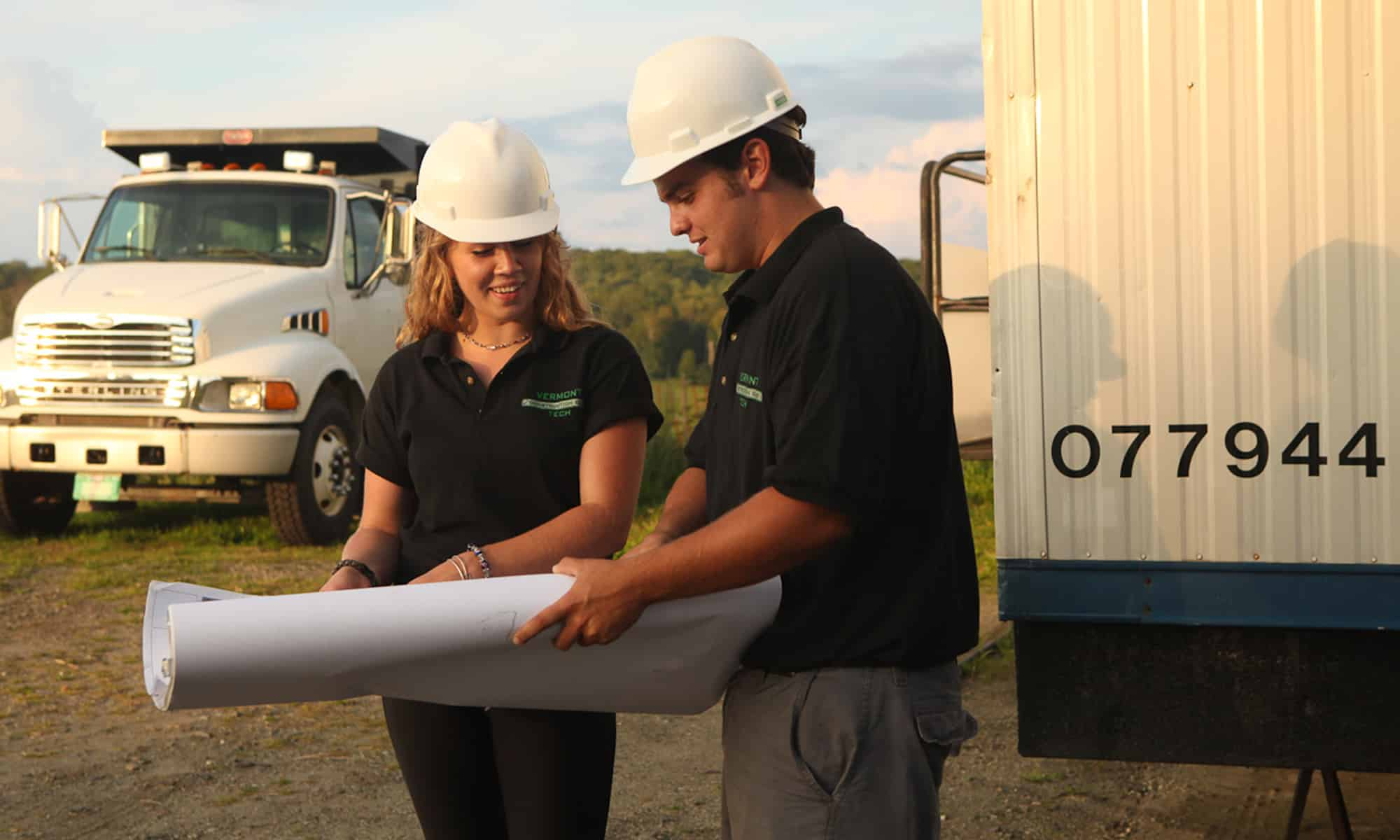 Two construction management students work on the job site and read construction plans together.