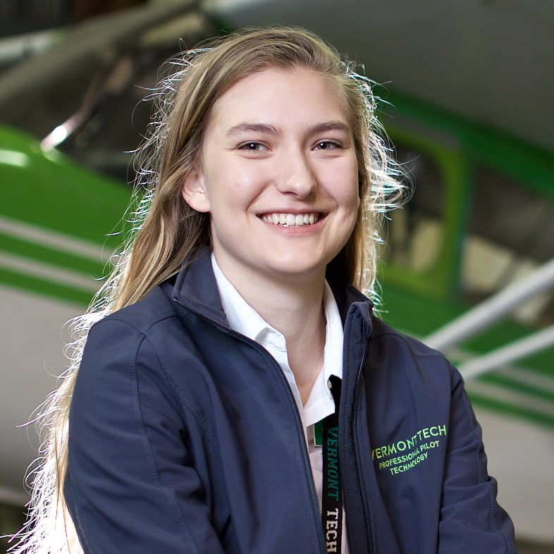 Female student Elisabeth Hoehn smiles in front of the plane that she flies while a student in the professional pilot technology program on the Williston campus.