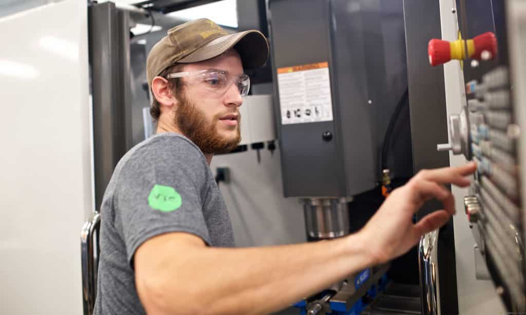 Male student runs a HAAS machine in the mechanical engineering lab on the Randolph Center campus.