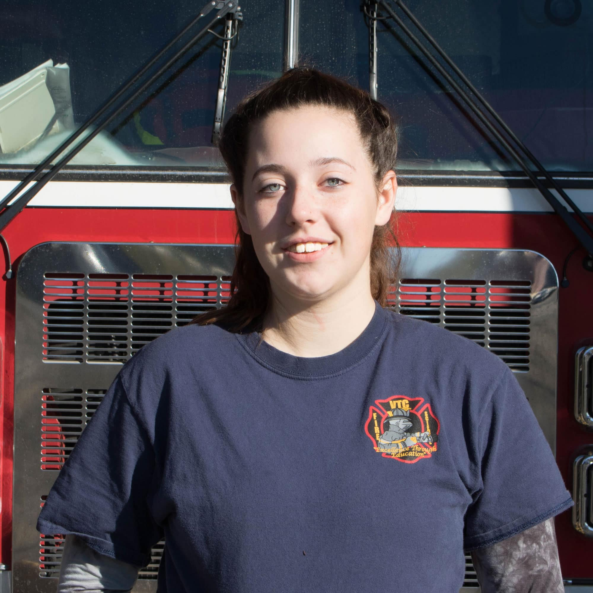 Courtney Clark smiles for camera in front of the fire truck
