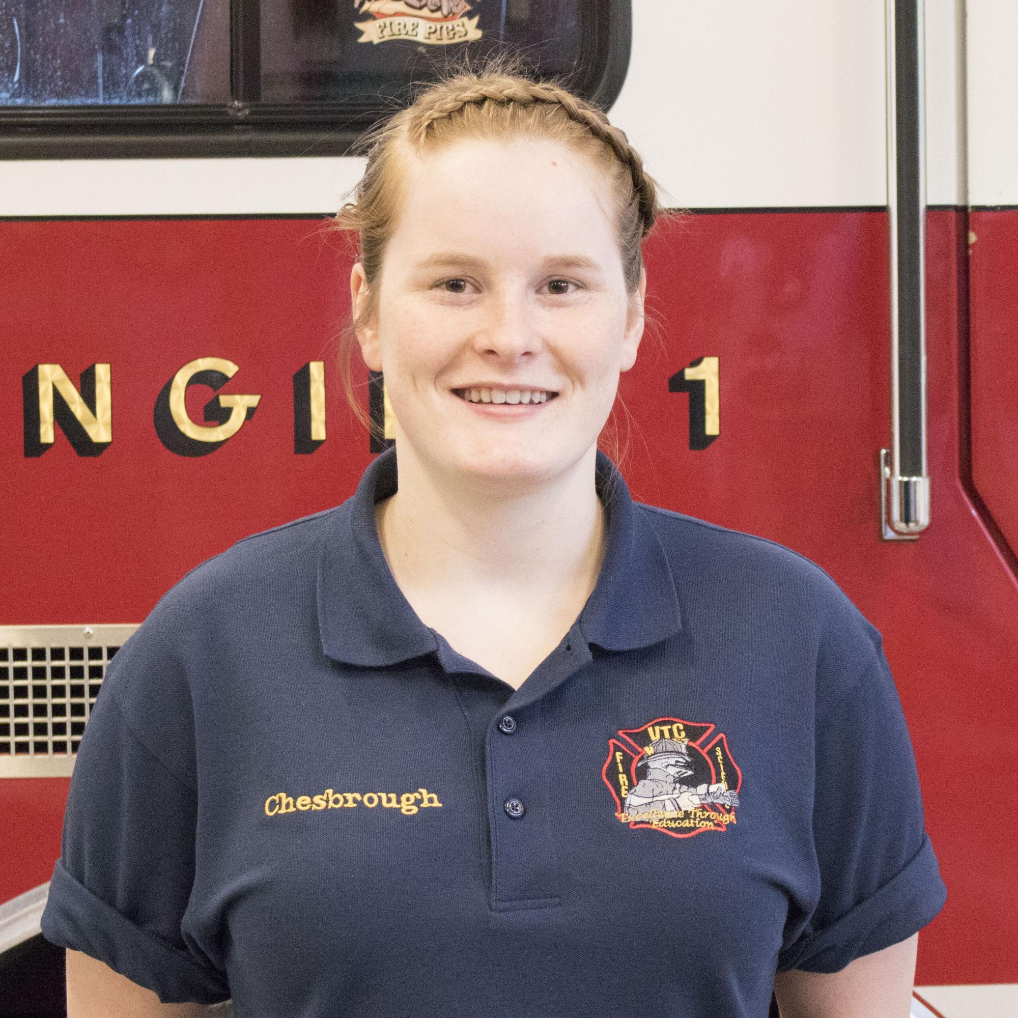 Female student stands in front of fire truck on the Randolph Center campus.