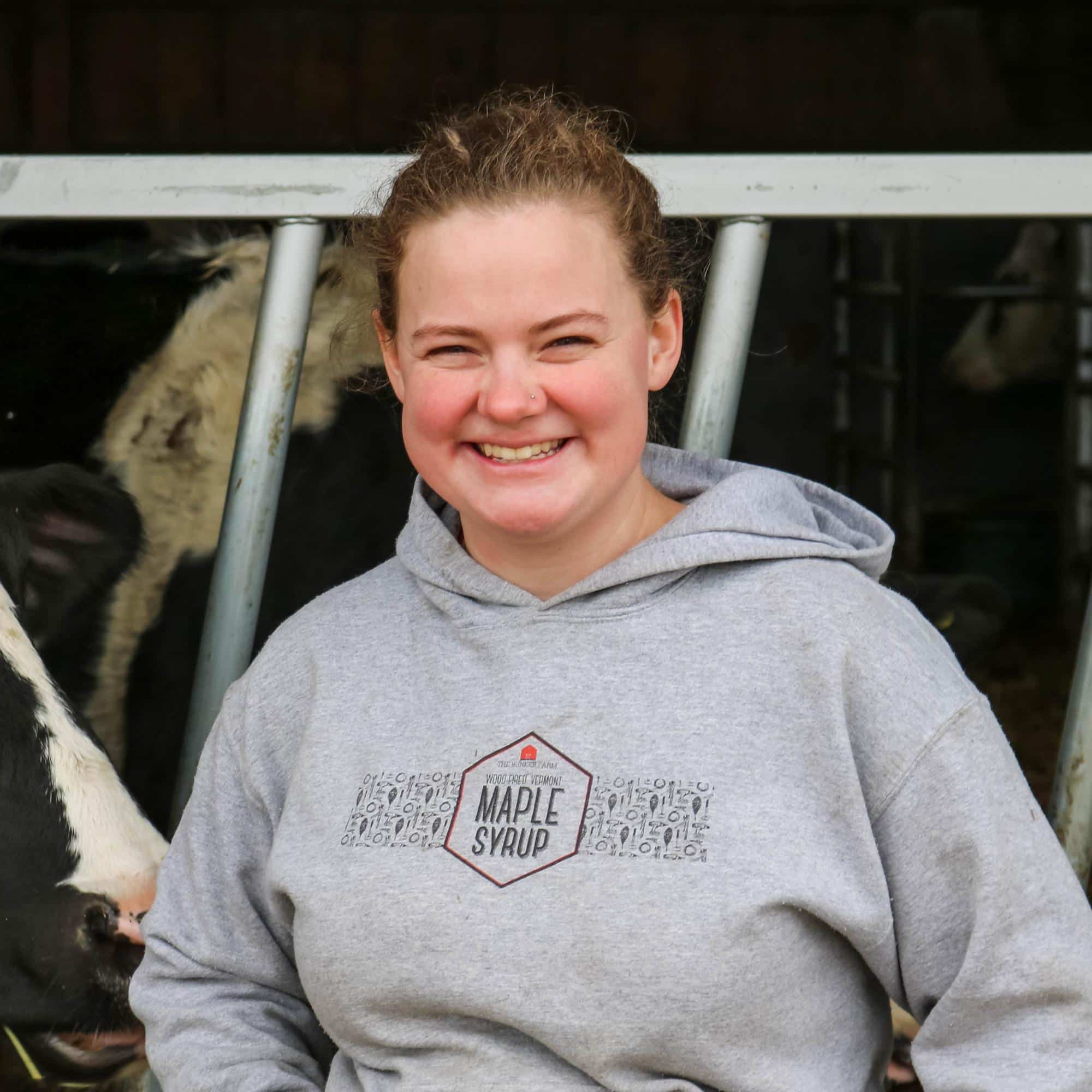 Louie Terrwilliger smiles at the camera with cows in the background at the barn