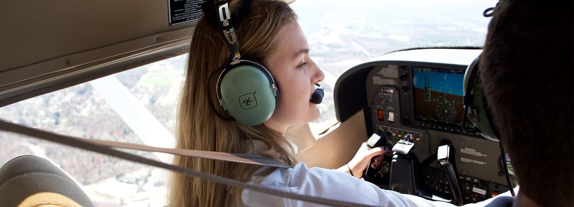 A female student adjusts controls on a plane dashboard as she soars above the Burlington area, professional pilot technology, pilot, STEM, hands on