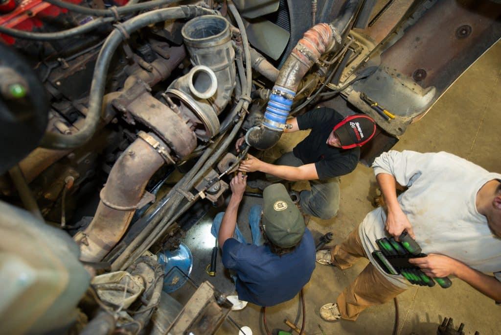 Three Vermont Tech students work on a large truck diesel engine, lab, Randolph Center campus