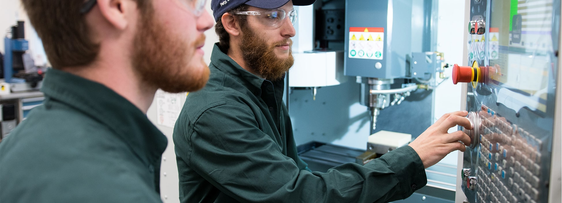 Students operate a large piece of manufacturing equipment during Manufacturing Day on the Randolph Center campus