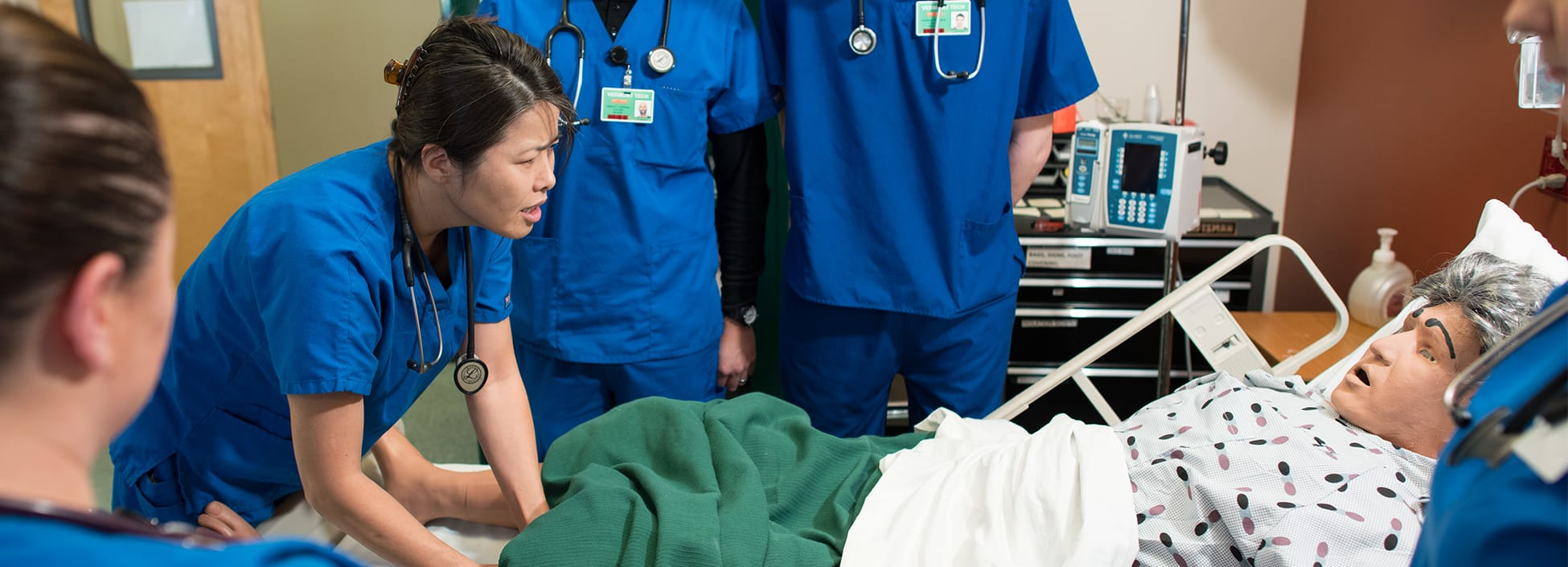 A group of nursing students examines a simulation patient during lab, hands on, Williston campus