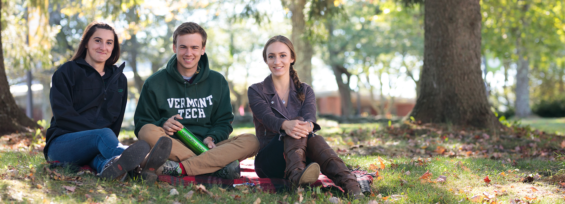 three students enjoy an afternoon on the lawn under the trees, smiling, Randolph Center campus
