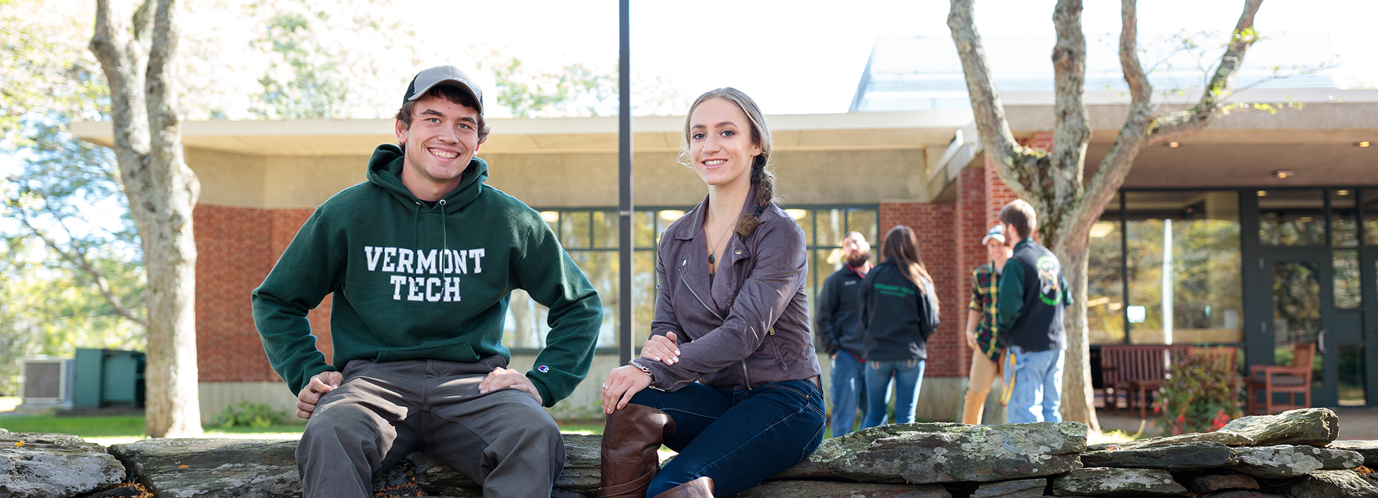 students smile and relax by the library on the stone wall, Randolph Center campus