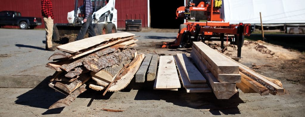 Piles of wood planks that have been planed from a tree lie on a pallet in front of saw, Randolph Center campus, forestry