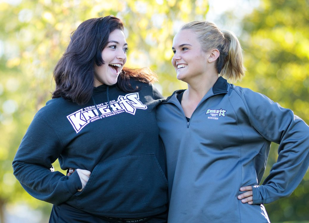 Two female students smile at each other while posing for a fun photo, outside, Randolph Center campus
