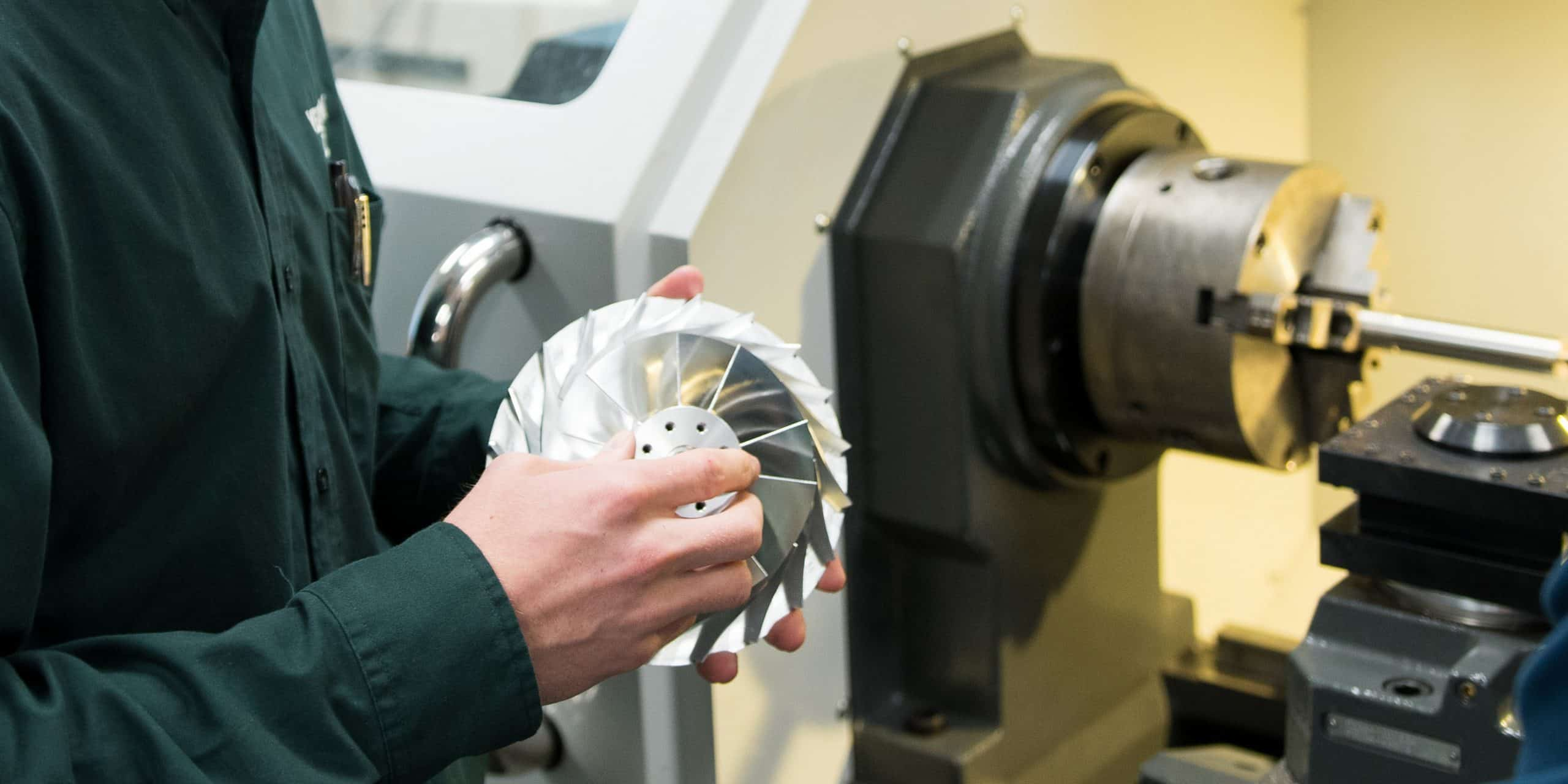 A machined part made from the lathe machine in the background, hand holding part