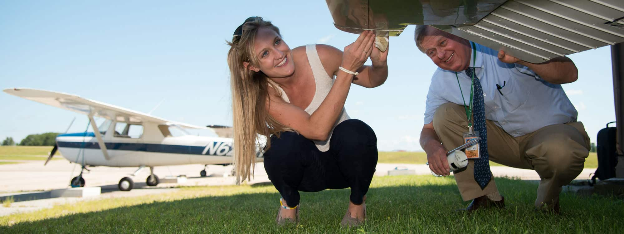 Jamie Heiam, Professional Pilot Technology student, inspects a plane with her instructor on the Williston Campus