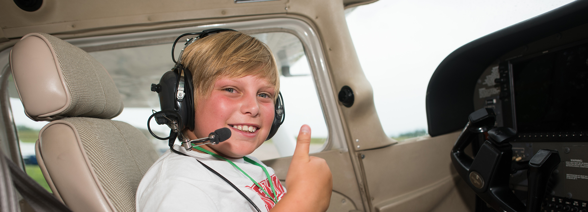 AeroCamp student looks excited to be in the cockpit! Professional Pilot technology, youth, camp, STEM