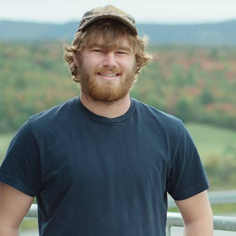 Brad Remillard, student, wears hat and smiles in front of scenic view