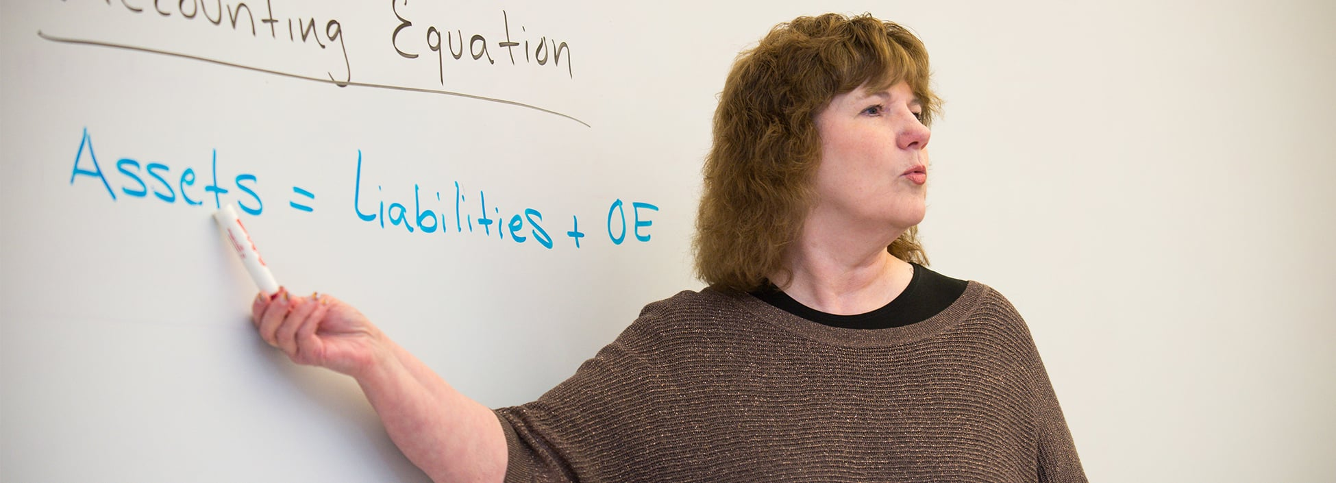 Professor Joyce Twing teaches economics to a class of first-year students, business technology and management