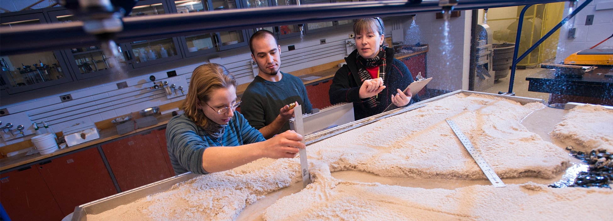 Civil students measure gullies and water flow with the sand table, hands on, engineering, STEM