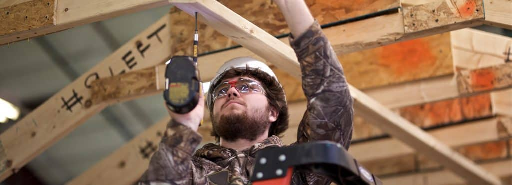 a construction student works to deconstruct a shed