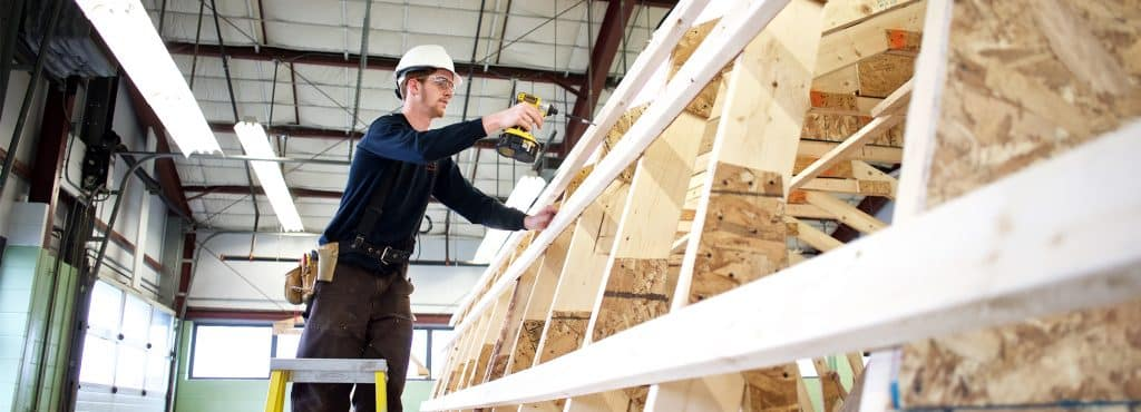 A construction student works on deconstructing a shed