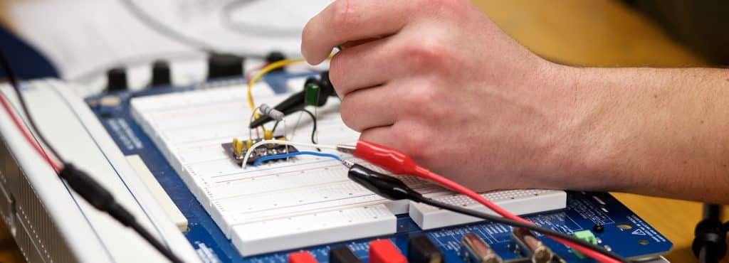 a student wires his final project, electrical engineering, hands sodering