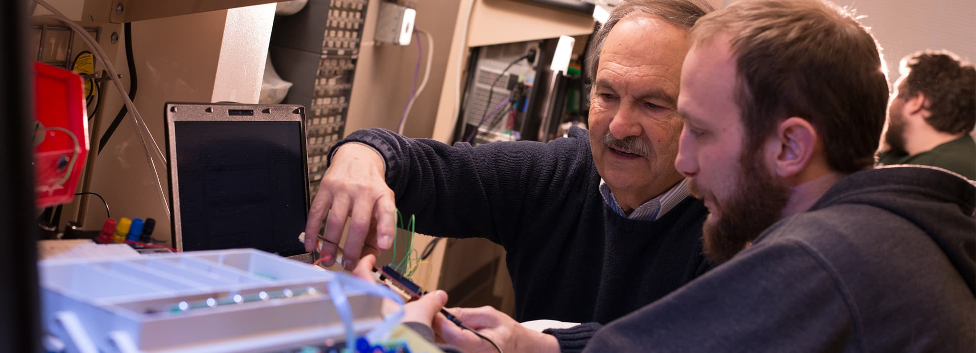 A professor works with an Electrical Engineering Technology student during lab, hands on