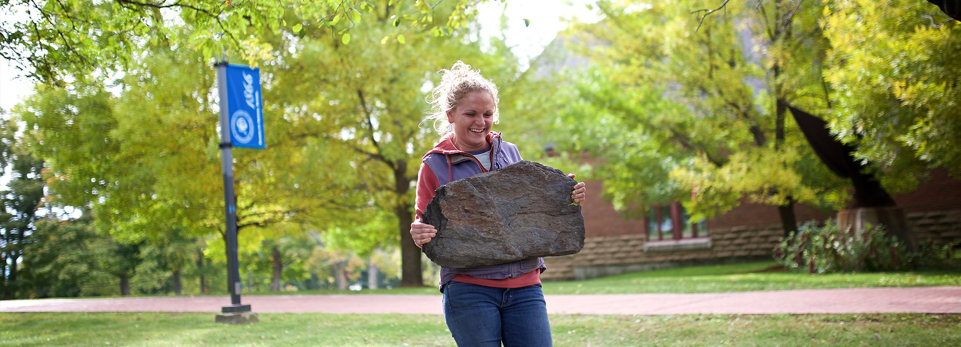 A landscape student carries a rock while learning to build a rock wall formation, female student, smiling, landscape contracting