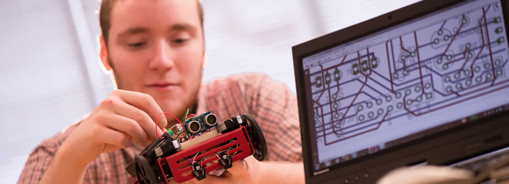 An Electromechanical Engineering Technology students works with a remote car in lab