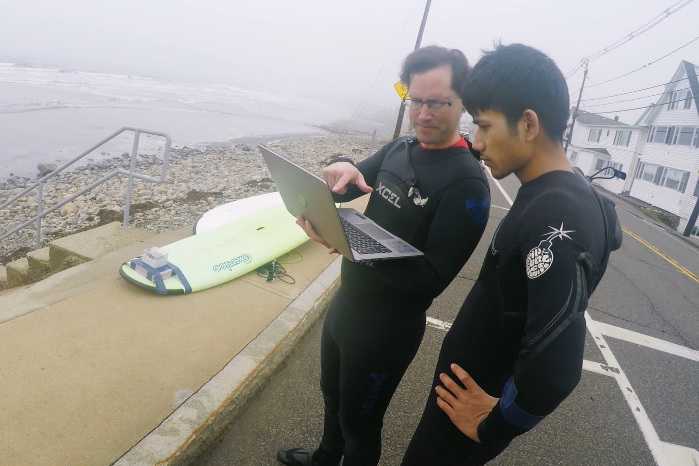 Josh and Puspa stand near the beach with a laptop, analyzing the data from their surfboard tracker, senior project
