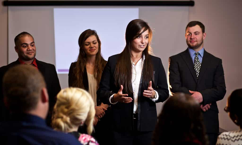 four students in business formal clothing present their senior projects to a crowd