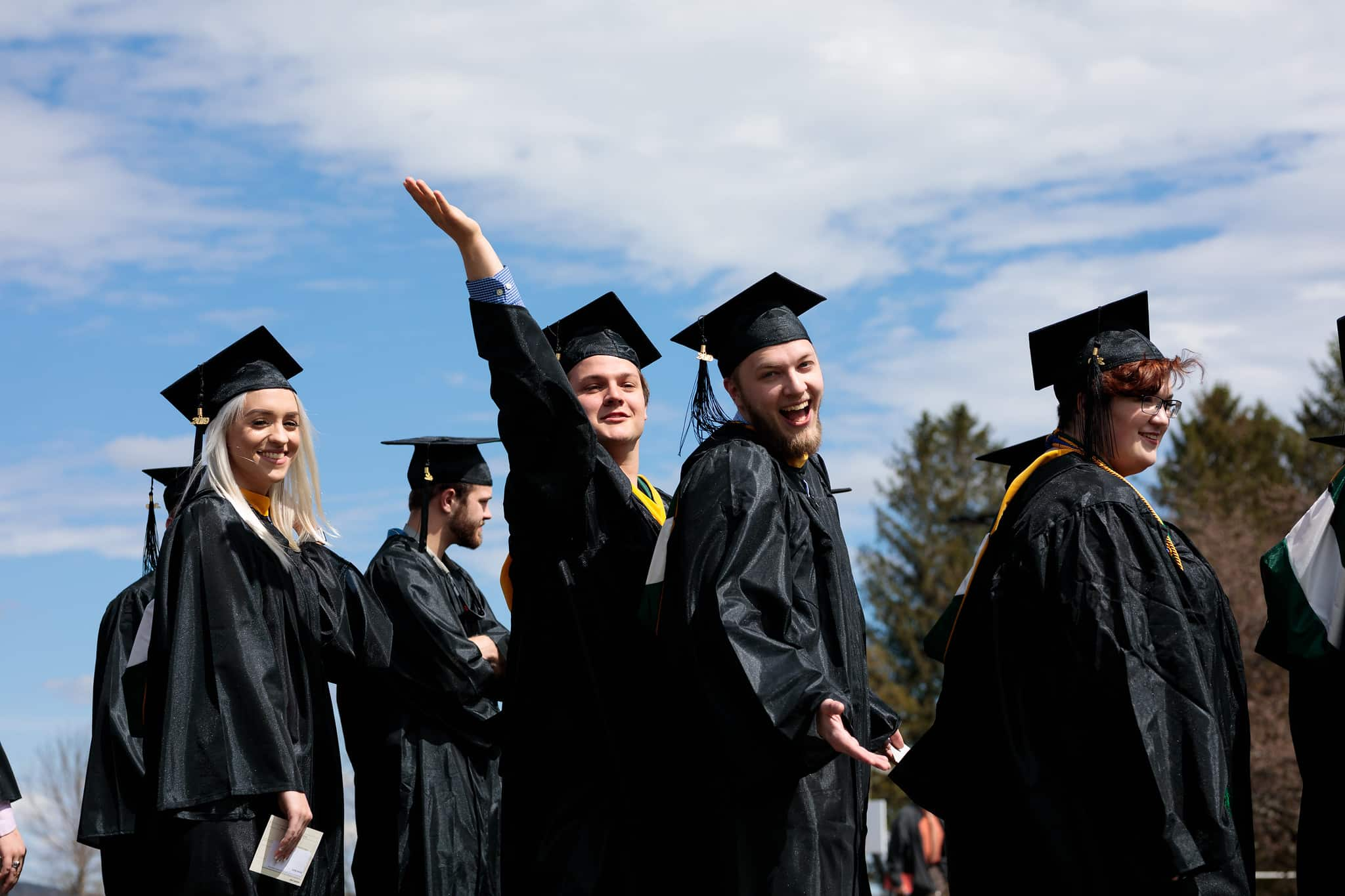 A recent Vermont Tech grad is waving as he processes with his fellow graduates in the graduation ceremony, wearing regalia
