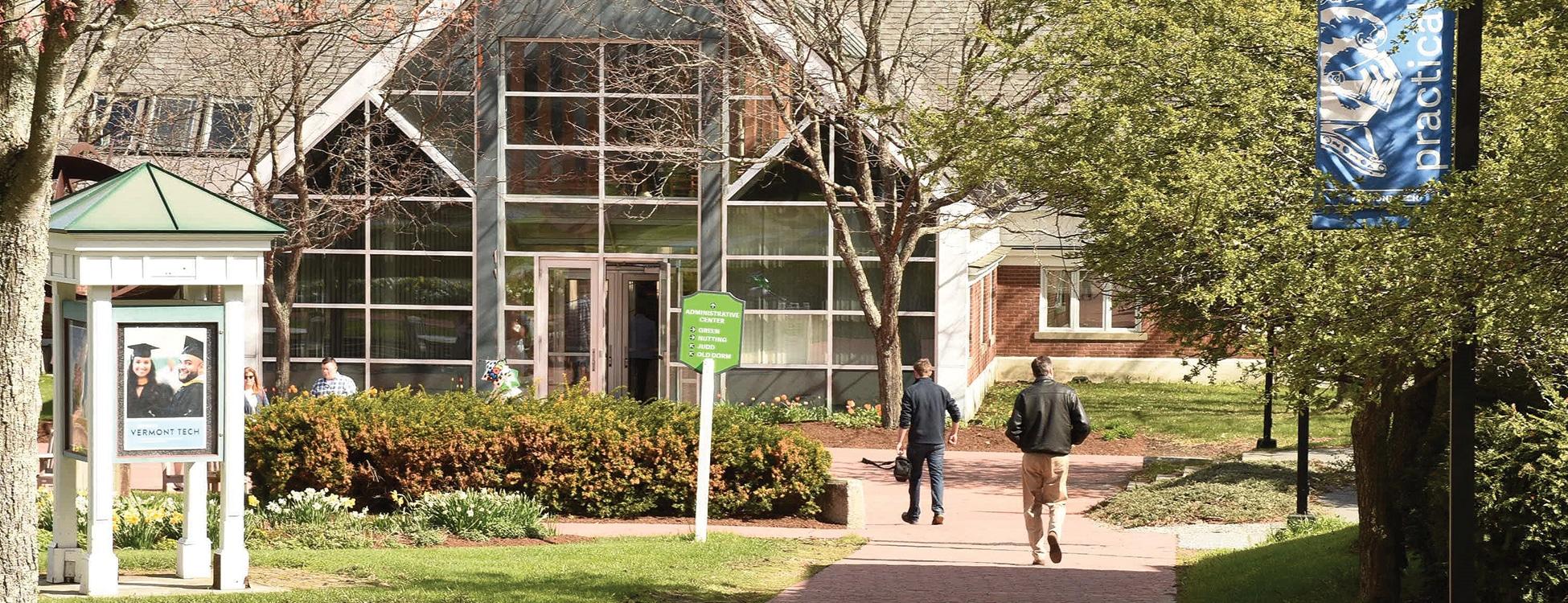 Students walk toward Administrative Building on Randolph Center campus
