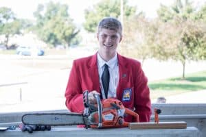 Austin Turco poses with his chainsaw before his presentation, SkillsUSA national competition