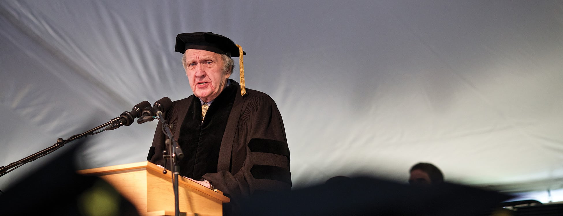Squier speaking at podium at commencement ceremony