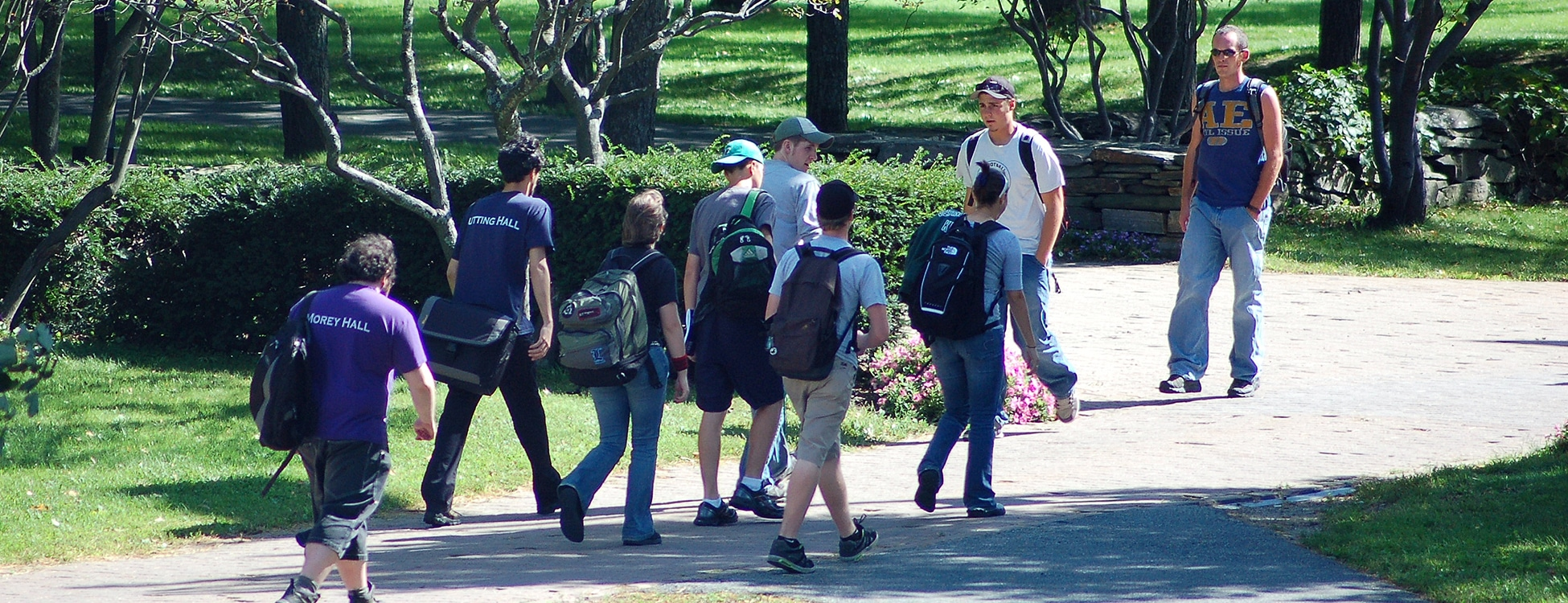 Students walk outside on walkway, sunshine, Randolph Center campus