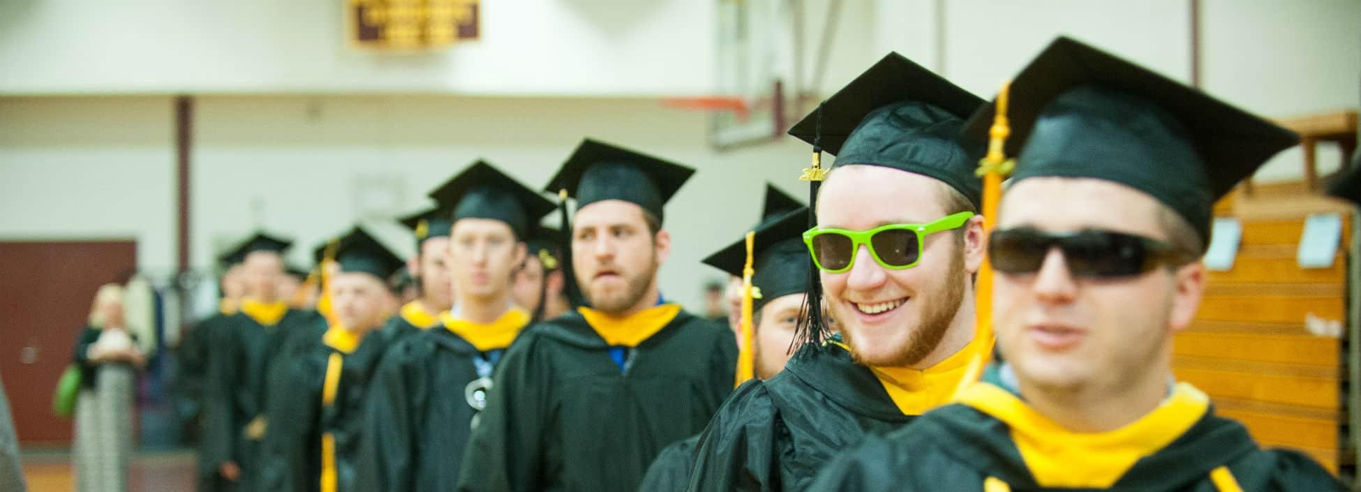 Graduates lining up for commencement, graduation, smiling, sunglasses, happy